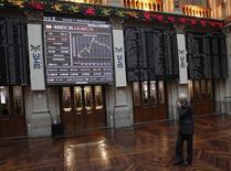 Трейдер смотрит на электронные табло на бирже Мадрида, 16 января 2012 г. Европейские рынки акций подросли в ходе торгов понедельника в преддверии заседания министров финансов еврозоны, которые обсудят условия сделки по списанию долгов Греции. REUTERS/Andrea Comas