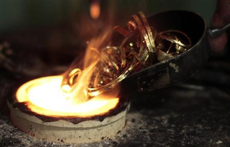A man melts down gold jewellery in Los Angeles, California August 23, 2011. REUTERS/Lucy Nicholson