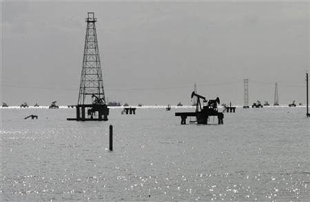 Oil rigs are seen on Lake Maracaibo from the shore in Cabimas, in Venezuela's western state of Zulia February 28, 2011. REUTERS/Isaac Urrutia