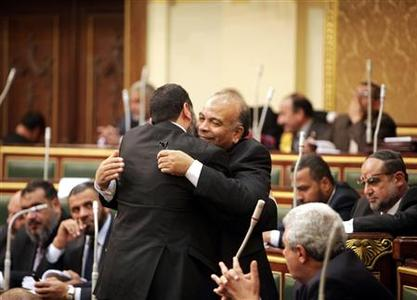 Mohamed Saad al-Katatni (R), the Muslim Brotherhood parliament member, greets another member of parliament during the first Egyptian parliament session after a revolution ousted former President Hosni Mubarak in Cairo January 23, 2012. REUTERS/Asmaa Waguih