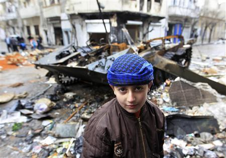 A Syrian boy stands in front of a damaged armoured vehicle belonging to the Syrian army in a street in Homs, January 23, 2012. REUTERS/Ahmed Jadallah