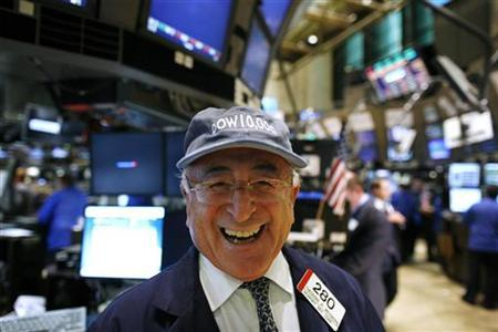 Trader Theodore Weisberg smiles as he wears a hat from March 1999, the first time the Dow rose above 10,000, on the floor of the New York Stock Exchange, October 14, 2009. REUTERS/Brendan McDermid