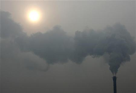 A chimney billows smoke as the sun shines through haze on a cold winter's day in Beijing December 24, 2009. REUTERS/David Gray