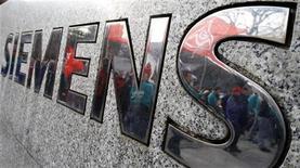 Сотрудники Siemens отражаются в логотипе компании в Берлине 26 ноября 2009 года. Немецкий промышленный гигант Siemens сообщил о 23-процентном снижении базовой операционной прибыли в первом квартале, разочаровав даже наиболее пессимистично настроенных аналитиков. REUTERS/Tobias Schwarz