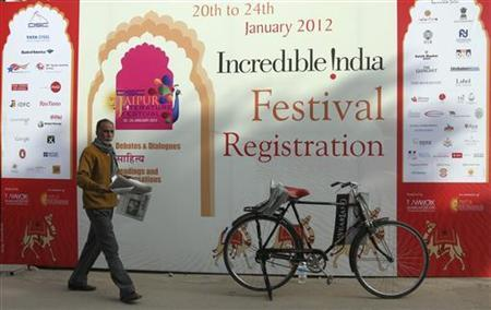 A newspaper vendor walks past an advertisement hoarding outside the venue of the annual Literature Festival in Jaipur January 22, 2012. REUTERS/Altaf Hussain