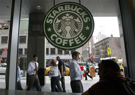 People walk past the Starbucks outlet on 47th and 8th Avenue in New York in this June 29, 2010 file photo.  REUTERS/Lily Bowers/Files