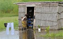 A woman enters her flooded home, near the swollen Limpopo River in Mozambique, January 25, 2011.  REUTERS/Grant Lee Neuenburg