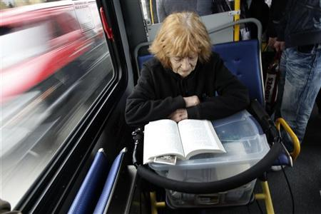 An elderly woman reads a book on a bus in Burnaby, British Columbia June 16, 2011. REUTERS/Jason Lee