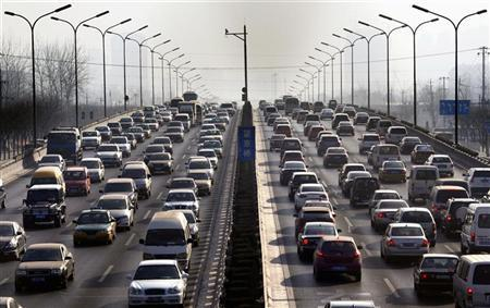 Cars drive along a main road in central Beijing January 12, 2012. Car sales in China climbed 5.2 percent in 2011, the slowest pace since the nation's car culture took off at the turn of the century, as consumers shunned local brands after Beijing scrapped tax incentives for small cars. REUTERS/David Gray