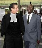 <p>Leon Mugusera (R) and his lawyer Guy Bertrand walk out of court in Quebec City in this April 12, 2001 file photo. REUTERS/Didier Debusschere</p>
