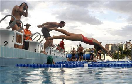 Participants jump into a swimming pool during a weekly, after-work biathlon that gathers a few hundred professionals including lawyers, bankers and accountants, at The Domain adjacent to Sydney's central business district November 20, 2008. REUTERS/Tim Wimborne