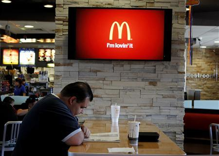 Customer Steven Price sits at a table near a HDTV screen showing the new McDonald's Channel at a McDonald's restaurant in Norwalk, California in this file photo taken October 17, 2011.     REUTERS/Fred Prouser/Files