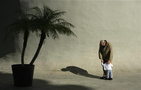 An elderly man hugs a boy in the Andalusian capital of Seville January 18, 2012.  REUTERS/Marcelo del Pozo