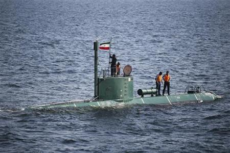 Military personnel place a flag on a submarine during the Velayat-90 war games by the Iranian navy in the Strait of Hormuz in southern Iran December 27, 2011. REUTERS/IIPA/Ali Mohammadi