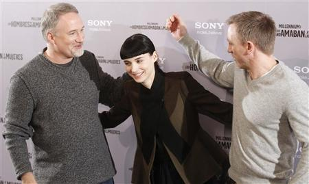 Cast members Daniel Craig (R) and Rooney Mara pose with director David Fincher (L) during the media presentation of their movie ''The Girl with the Dragon Tattoo'' in Madrid January 4, 2012. REUTERS/Andrea Comas