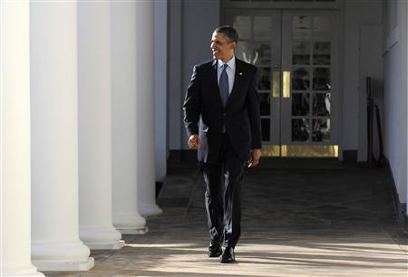 President Obama smiles as he responds to a reporter's question while walking along the colonnade outside the Oval Office at the White House, January 24, 2012. REUTERS/Jonathan Ernst