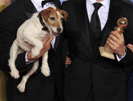 Uggie, the dog featured in ''The Artist''  is held next to the Golden Globe award the film  won as best comedy or musical motion picture at the 69th annual Golden Globe Awards in Beverly Hills, California, January 15, 2012. REUTERS/ Lucy Nicholson