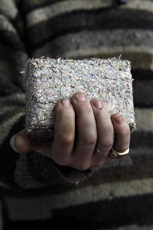 Irish artist Frank Buckley holds a brick made of 50,000 euros in decommissioned euro notes from the Irish Central Bank's mint, in Dublin January 24, 2012.  REUTERS/Cathal McNaughton