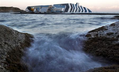 The Costa Concordia cruise ship which ran aground off the west coast of Italy at Giglio island lies on its side, half-submerged and threatening to slide into deeper waters January 24, 2012. REUTERS/Tony Gentile