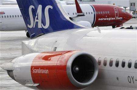 A Norwegian Air's Boeing 737-800 aircraft prepares for takeoff behind a SAS MD-82 aircraft parked at gate on Terminal 5 at Arlanda airport, north of Stockholm February 9, 2010. REUTERS//Johan Nilsson/Scanpix