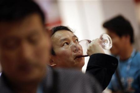 A man drinks a glass of red wine of the Sarome Bordeaux vineyard from France during the 6th Shanghai International Wine Trade Fair June 1, 2011. REUTERS/Carlos Barria