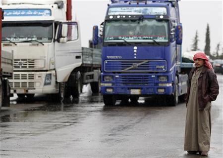 A driver stands next to the trucks lined at the Oncupinar borger crossing on the Turkish-Syrian border in the southeastern city of Kilis January 13, 2012. REUTERS/Umit Bektas