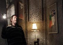"""Ирландский художник Фрэнк Бакли в доме, построенном из остатков утилизированных банкнот Евросоюза общей стоимостью 1,4 миллиарда евро, 24 января 2012 г. Безработный ирландский художник построил дом из остатков утилизированных банкнот Евросоюза общей стоимостью 1,4 миллиарда евро, по его словам, - памятник """"сумасшествию"""", которое охватило Ирландию после введения в стране евро. REUTERS/Cathal McNaughton"""