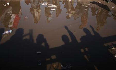 Demonstrators are seen reflected on water during a protest marking the first anniversary of Egypt's uprising at Tahrir square in Cairo January 25, 2012. REUTERS/Suhaib Salem