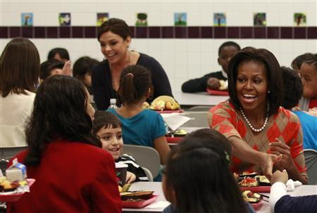 First Lady Michelle Obama has lunch with students at Parklawn Elementary School in Alexandria, Virginia January 25, 2012. At the table behind is celebrity cook Rachael Ray. Obama made the visit to speak about the United States Department of Agriculture's (USDA) new and improved nutrition standards for school lunches. REUTERS/Kevin Lamarque