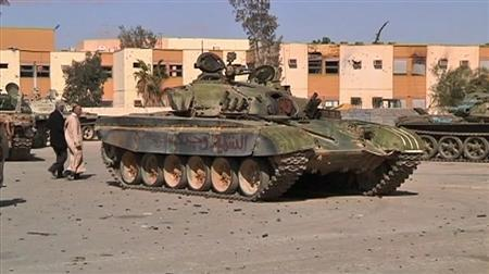 A damaged tank is seen after an attack by armed Gaddafi loyalists in Bani Walid, a town about 200 km (120 miles) from Tripoli, in this still image taken from video January 24, 2012. A bullet-scarred barracks, scorched and abandoned like the ageing tanks guarding its shattered gateway, was all that remained on Tuesday of what passed for the Libyan government's grip on Bani Walid. REUTERS/via Reuters TV