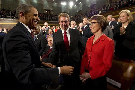 U.S. President Barack Obama (L) greets Representative Gabrielle Giffords (D-AZ), who was shot in the head during a shooting spree in Tucson, Arizona, in January, 2011, as members of Congress applaud prior to the president's State of the Union address to a joint session of Congress on Capitol Hill in Washington, January 24, 2012. Giffords is expected to formally resign from Congress on January 25. REUTERS/Saul Loeb/Pool