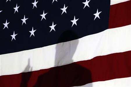 Republican presidential candidate and former Speaker of the House Newt Gingrich is silhouetted against the U.S. flag during his speech at a Space Coast meeting in Cocoa, Florida January 25, 2012.  REUTERS/Shannon Stapleton