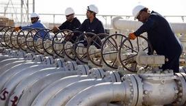 Рабочие закручивают вентили нефтепровода на месторождении Западная Курна в иракской провинции Басра 28 ноября 2010 года. Нефть Brent превысила уровень $110 за баррель в четверг в надежде на восстановление роста спроса, после того как ФРС США заявила, что намерена удерживать ключевую ставку без изменений намного дольше, чем рассчитывал рынок. REUTERS/Atef Hassan