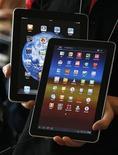 Сотрудник южнокорейского сотового оператора KT держит планшетные компьютеры Galaxy Tab 10.1 от компании Samsung Electronics (на переднем фоне) и iPad компании Apple Inc в Сеуле 10 августа 2011 года. Европейские акции растут в четверг после того, как ФРС США заявила, что ключевая ставка останется низкой намного дольше, чем ожидалось раньше, и выразила готовность предложить дополнительные стимулы экономике. REUTERS/Jo Yong-Hak