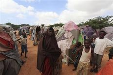 <p>Kadija Mohamed (C) walks through a camp set up for internally displaced people in Dinsoor, January 5, 2012. REUTERS/Feisal Omar</p>