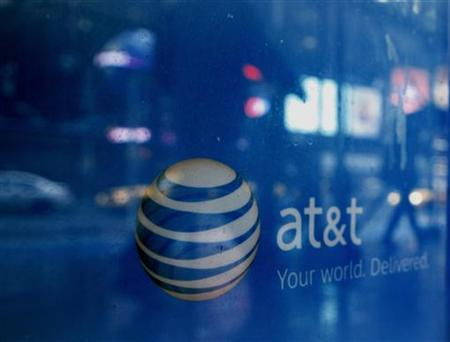 Reflections are seen in the window of an AT&T store in New York March 21, 2011. REUTERS/Brendan McDermid/Files