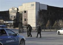 Солдаты внутренних войск Казахстана 19 декабря 2011 года патрулируют улицу в Жаназене на фоне здания, поврежденного огнем в ходе кровопролитных столкновений демонстрантов с полицией. Власти Казахстана возложили ответственность за столкновения демонстрантов с полицией в нефтяном городе Жанаозен в декабре прошлого года на нескольких офицеров МВД, градоначальника, а также на деятелей оппозиции, которая назвала трагедию предлогом для расправы с политическими оппонентами. REUTERS/Vladimir Tretyakov
