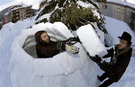 Members of the Occupy WEF movement use blocks of snow to build an igloo at their camp site in the Swiss mountain resort of Davos January 22, 2012.  REUTERS/Arnd Wiegmann