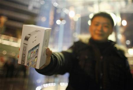 A customer show his new iPhone 4S after making the purchase at Apple's retail store in downtown Shanghai January 13, 2012. REUTERS/Carlos Barria