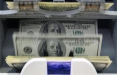 Американские банкноты в аппарате для счета денег в банке в Берне 15 августа 2011 года. Рубль подешевел в начале торгов пятницы к доллару, отыграв его восстановление на форексе, снизился к бивалютной корзине на фоне замедления глобального спроса на риск и возможной фиксации прибыли перед выходными днями. REUTERS/Pascal Lauener