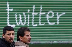 Поддерживающие оппозицию мужчины разговаривают на фоне граффити с названием сети микроблогов Twitter на площади Тахрир в Египте 5 февраля 2011 года. Twitter начнет ограничивать записи в некоторых странах, сообщила интернет-компания в четверг вечером, вновь вызвав вопросы о том, насколько социальные сети обеспечивают свободу высказываний на фоне быстро растущего числа пользователей. REUTERS/Steve Crisp