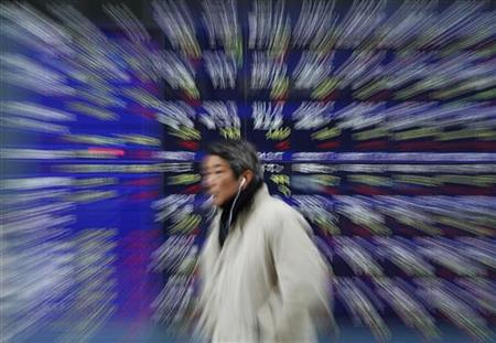 A man walks past a stock quotation board showing Japanese companies' stock prices outside a brokerage in Tokyo December 1, 2011. REUTERS/Kim Kyung-Hoon/Files