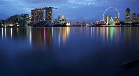 Lights of the skyline of the central business district and Marina Bay are reflected on the waters of Marina Barrage in Singapore at dusk, December 1, 2011. REUTERS/Tim Chong