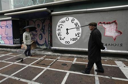 People walk in front of a closed shop with graffiti on it in central Athens January 24, 2012. REUTERS/John Kolesidis