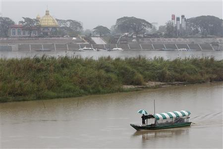 A man stands on a small boat travelling along the Mekong river in front of the Kings Roman casino opposite Sop Ruak in the Golden Triangle region where the borders of Thailand, Laos and Myanmar meet January 14, 2012. REUTERS/Sukree Sukplang