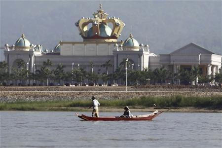 People maneuvre a small boat along the Mekong river in front of the Kings Roman casino opposite Sop Ruak in the Golden Triangle region where the borders of Thailand, Laos and Myanmar meet January 15, 2012. REUTERS/Sukree Sukplang