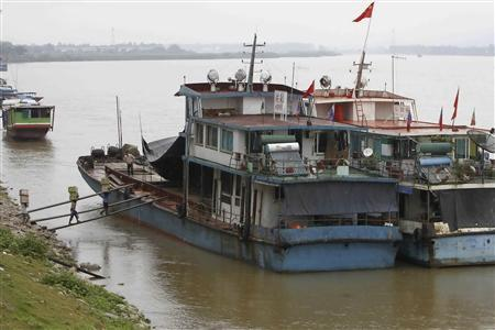 Workers load a Chinese boat at the Thai Mekong river port of Chiang Saen in the Golden Triangle region where the borders of Thailand, Laos and Myanmar meet January 14, 2012.  REUTERS/Sukree Sukplang