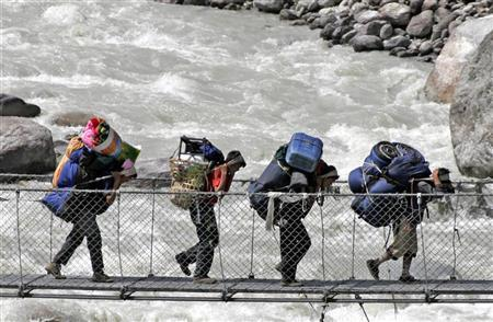 Porters walk across a bridge over the Bhote Koshi river in the Everest region May 29, 2007.  REUTERS/Shruti Shrestha