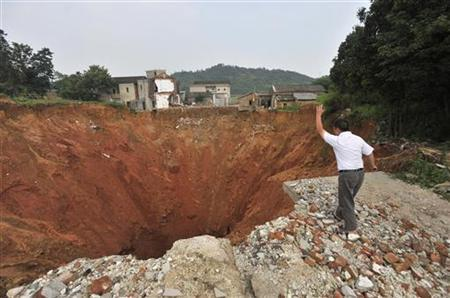 A local resident throws a stone into a sinkhole near Qingquan primary school in Dachegnqiao town of Ningxiang, Hunan province June 15, 2010. REUTERS/Stringer