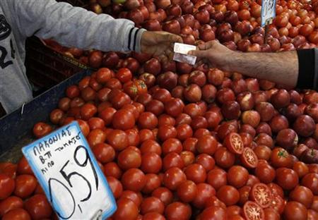A man buys tomatoes from a grocery shop at Athens main food market December 16, 2011. REUTERS/Yiorgos Karahalis/Files